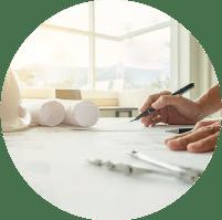 תמונת אווירה לקטגוריית ארכיטקטורה, קסדה לבנה של עובדי בניין, תכניות מגולגלות על שולחן שרטוט ויד מחזיקה כלי כתיבה
