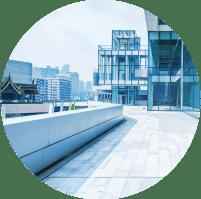 תמונת אווירה לקטגוריית צילום אדריכלי. בתמונה בנייני עסקים עם קירות זכוכית ומזרקת נוי מבטון מבחוץ.
