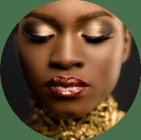 תמונת אווירה לקטגוריית האיפור האומנותי. בתמונה אישה עם עור בגוון שוקולד מאופרת בגוונים של זהב מלכותי