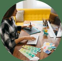 תמונה מייצגת לקטגוריית הצילום העסקי. בתמונה אישה מרוכזת יושבת מול המחשב, ביד אחת שולטת על המקלדת והיד השנייה מחזיקה עט על לוח גרפי. על שולחן העץ שמולה מונחת מניפת צבעים ומסך מחשב מאק גדול.