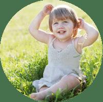 תמונה מקסימה המייצגת את קטגוריית צילומי משפחה. בתמונה פעוטה כבת שנה יושבת בשמלה לבנה ויחפה על הדשא, מביטה בחיוך כובש למעלה ועולה מוצפת בסינוור עדין של קרני שמש.