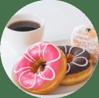 תמונה מייצגת לתחום צילום המזון. בתמונה כוס קפה ולצידה סופגניה אחת עם אבקת סוכר ושוקולד ושני דונאטס בציפויים שוקולד חום ותות ורוד עם עיטור לבן בצורת פרח עליהם.