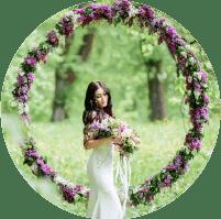 תמונת אווירה לקטגוריית איפור לאירועים. בתמונה כלה מחזיקה זר פרחים עם מבט נוסטלגי על רקע מיוער כשסביבה מסגרת עגולה ענקית שזורת פרחים סגולים