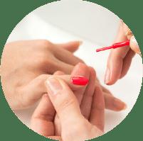 תמונת אווירה לקטגוריית עיצוב ציפורניים. בתמונה רואים תקריב של כפות ידיים, פעולה של מריחת לק אדום בוהק .