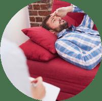 תמונת אווירה לקטגוריית הטיפול הפסיכותירפי. בתמונה אדם השוכב על ספה אדומה בחולצת משבצות מכופתרת ומניח יד אחת על המצח בדאגה כשמולו יושב אדם על כיסא ומחזיק דף ועט בידו
