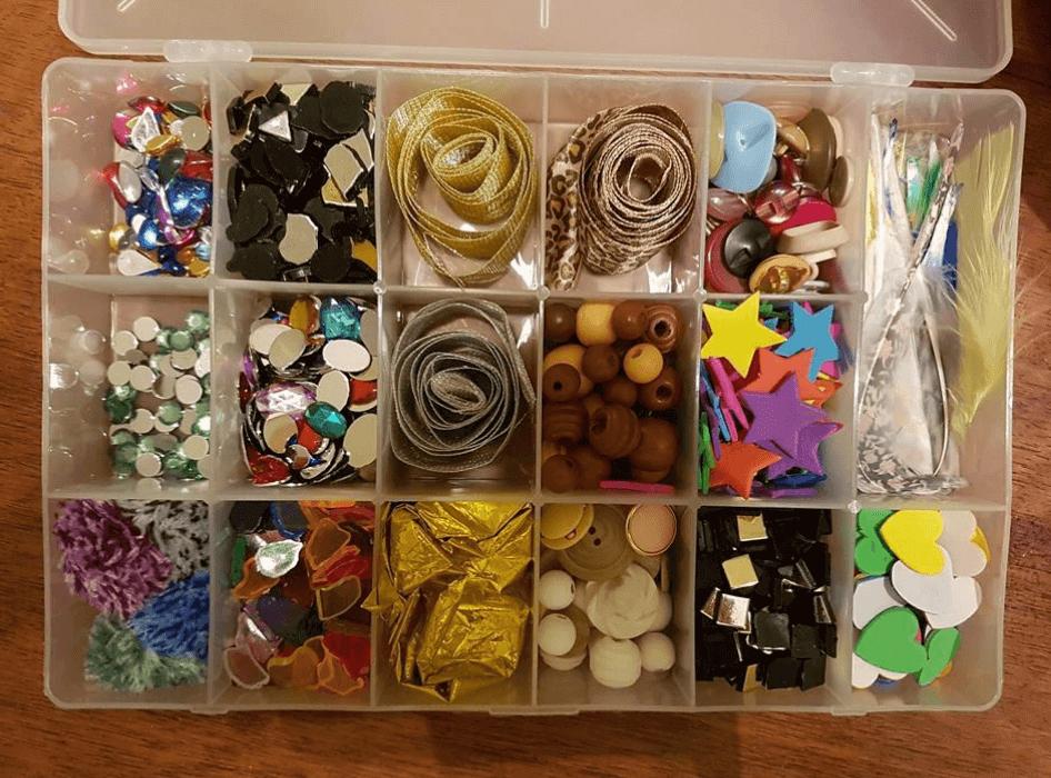 קופסא מלאה באלמנטים לקישוט בדים - כפתורים, חרוזים, נוצות, סרטים צבעוניים כחלק מקורס סטיילינג טיפולי בהנחיית עדי לנדאו רון