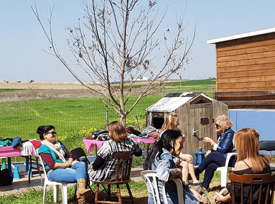 מפגש סטיילינג בו יושבות נשים בזוגות עם שתיה חמה בחצר על רקע אזור חקלאי כשלצידן שולחנות עמוסים בבגדים