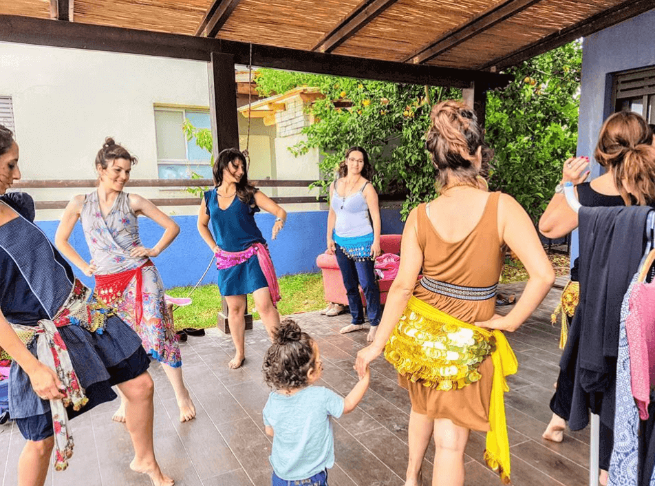 נשים עומדות במעגת על מרפסת עם דק מעץ ועושות תנועת ריקוד מזרחי עם בדים שזורים במטבעות שקשורים על המותניים כחלק מקורס סטיילינג טיפולי בהנחיית עדי לנדאו רון