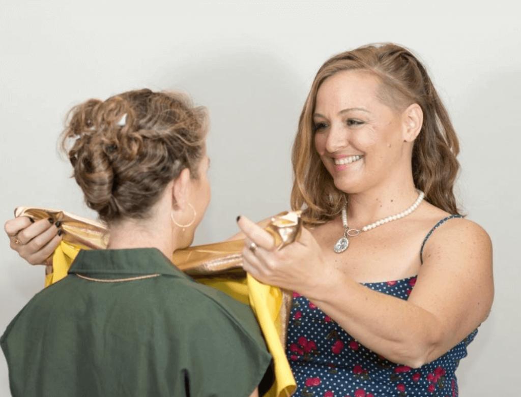 עדי לנדאו רון מודדת בד צהוב מבריק על צוואר של משתתפת בסדנא