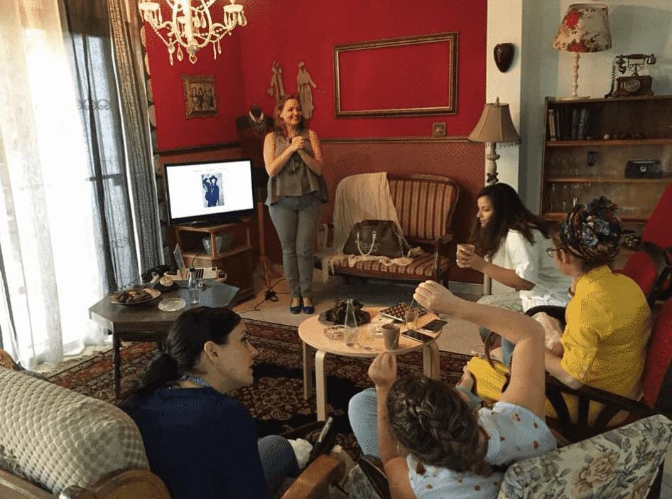 עדי לנדאו רון מרצה בסלון חמים ומעוצב בסגנון וינטאג׳ מול קבוצת נשים בקורס סטיילינג טיפולי