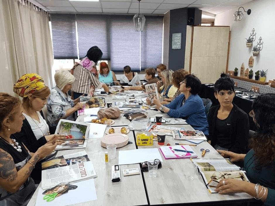 סדנת סטיילינג טיפולי, נשים יושבות סביב שולחן ארוך ומעיינות במגזינים ומקיימות דיון פורה