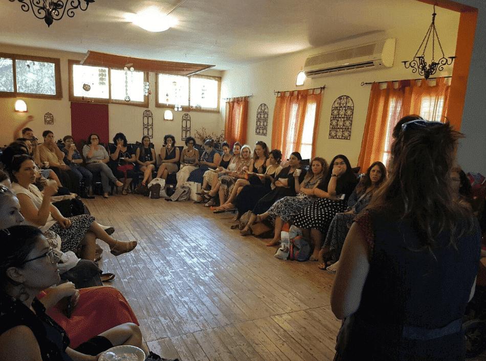 עדי לנדאו רון מרצה באולם מול עשרות נשים שמאזינות בשקיקה בנושא הסטיילינג הטיפולי