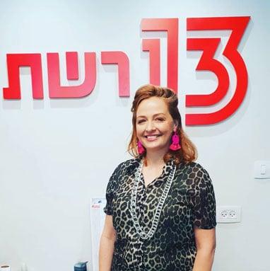 תמונה של עדי לנדאו רון כשמאחוריה לוגו ערוץ 13 של רשת, מתוך ראיון שהשתתפה בו