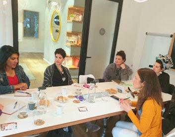 תמונה של 5 בנות יושבות סביב שולחן עם כרטיסיות בסדנת סטיילינג טיפולי בהנחיית עדי לנדאו רון