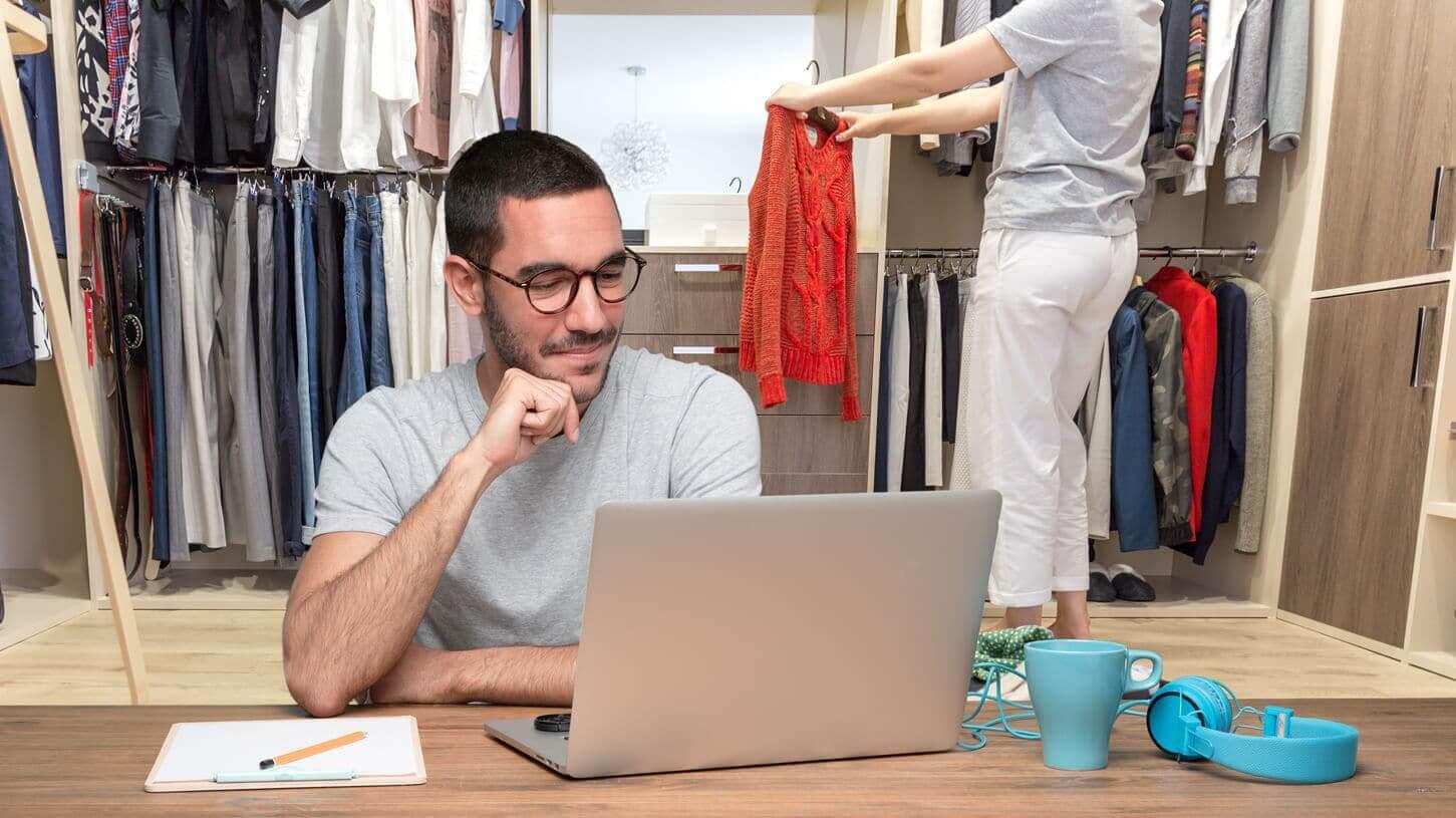 תמונת לפני - בחור יושב מול שולחן ולפטופ כשמאחוריו בלאגן של בגדים