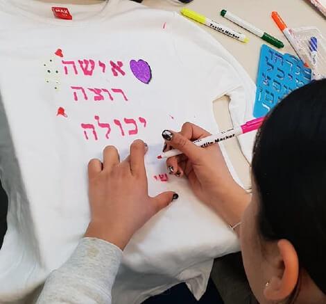 בתמונה נערה מציירת על חולצה את המשפט ״אישה רוצה יכולה..״ עם קישוטים מעצימים styling therapy סטיילינג טיפולי
