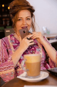 תמונה של עדי לנדאו רון שותה קפה ומחזיקה סמארטפון ביד styling therapy סטיילינג טיפולי