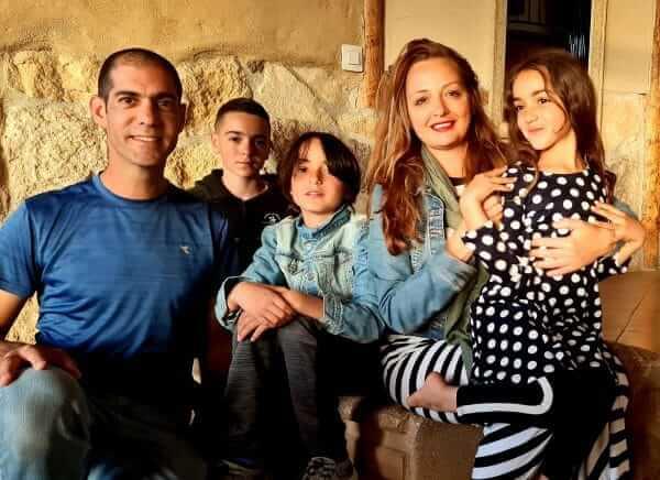 תמונה של עדי לנדאו רון ובני המשפחה על רקע הבית שעברו אליו במצפה רמון, משם ממשיכה לנהל את בית הספר לסטייליסטיות טיפוליות