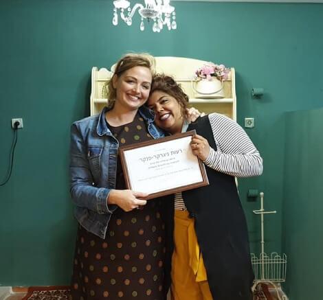 תמונה של עדי מחבקת תלמידה שסיימה את הקורס ומחזיקות יחד תעודת סיום styling therapy סטיילינג טיפולי